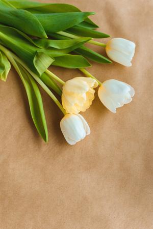 top view of beautiful tender tulip flowers with green leaves on craft paper Zdjęcie Seryjne