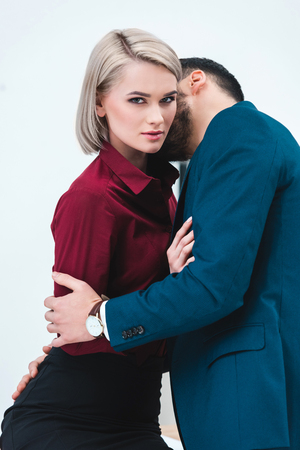 seductive young couple of business people kissing and flirting