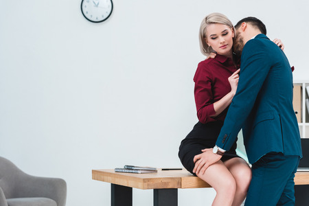 seductive young couple of business people flirting in office 免版税图像