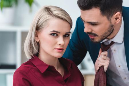 junge Geschäftsfrau, die in die Kamera schaut, während sie die Krawatte eines gutaussehenden Geschäftsmannes hält Standard-Bild