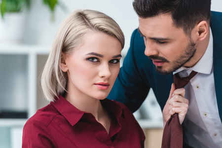 young businesswoman looking at camera while holding necktie of handsome businessman Foto de archivo