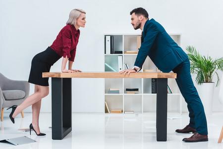 Vista lateral de jóvenes empresarios apoyados en la mesa y mirarse en la oficina