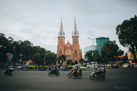HO CHI MINH, VIETNAM - 03 JANUARY, 2018: people riding motorbikes on road near church and modern buildings in Ho Chi Minh, Vietnam