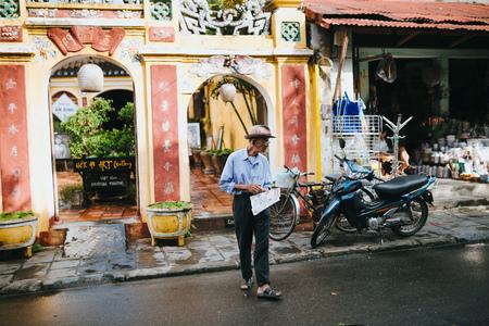 HOI AN, VIETNAM - 03 JANUARY, 2018: senior vietnamese man with newspaper walking on street in Hoi An, Vietnam
