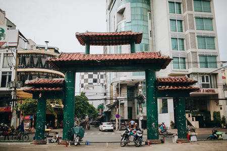 HO CHI MINH, VIETNAM - 03 JANUARY, 2018: traditional oriental gates and modern buildings on street of Ho Chi Minh, Vietnam