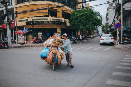 HO CHI MINH, VIETNAM - 03 JANUARY, 2018: vietnamese man carrying bicycle with bags and baskets on road in Ho Chi Minh, Vietnam
