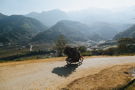 SA PA, VIETNAM - 03 JANUARY, 2018: person riding motorbike and carrying wood on mountain road, Sa Pa, Vietnam Redactioneel