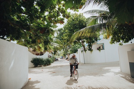 UKULHAS, MALDIVES - 27 JANUARY, 2018: man riding bicycle on street at  Ukulhas island, Maldives Editorial