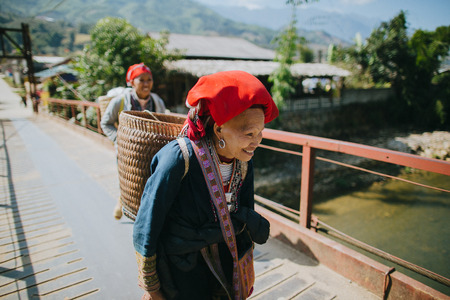 SA PA, VIETNAM - 03 JANUARY, 2018: vietnamese women carrying baskets and walking on bridge in Sa Pa, Vietnam
