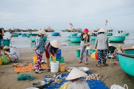 MUI NE, VIETNAM - 03 JANUARY, 2018: vietnamese fishermen with seafood on sandy beach at Mui Ne, Vietnam