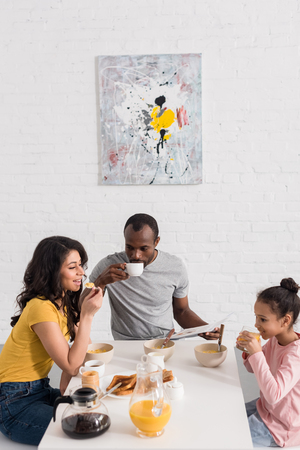 happy young family having breakfast on kitchen together