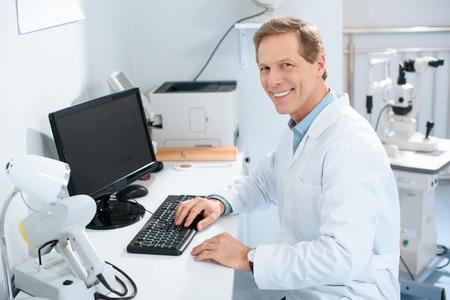 Guapo oftalmólogo masculino sonriente que trabaja con la computadora en la clínica Foto de archivo