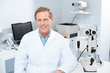 handsome smiling ophthalmologist looking at camera in consulting room Stok Fotoğraf