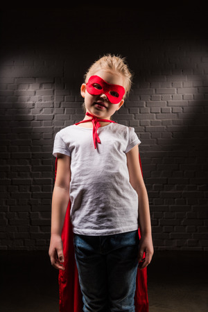 kid in superhero costume with red mask and cloak Stock Photo