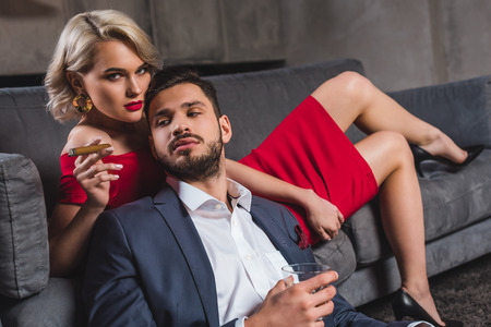 sensual stylish couple in suit and evening gown holding cigar and glass of whisky Stock fotó