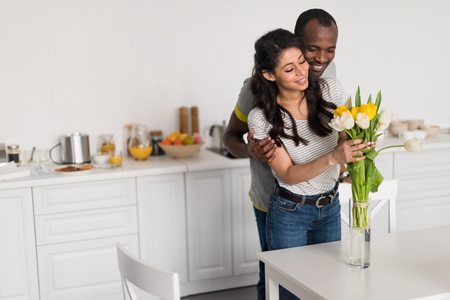 happy african american woman putting flowers bouquet into vase while her boyfriend embracing her from behind 写真素材