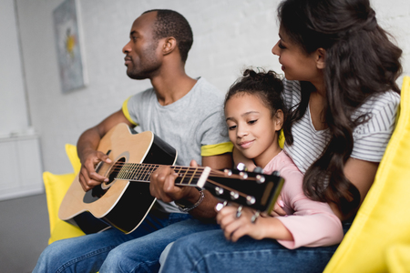 man playing guitar for wife and daughter at home