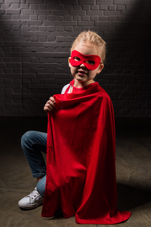 beautiful supergirl in red mask and cloak Stock Photo