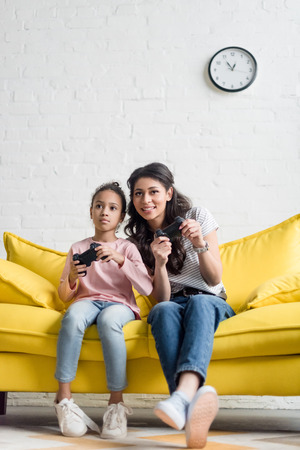 emotional young mother and daughter playing video games at home on couch