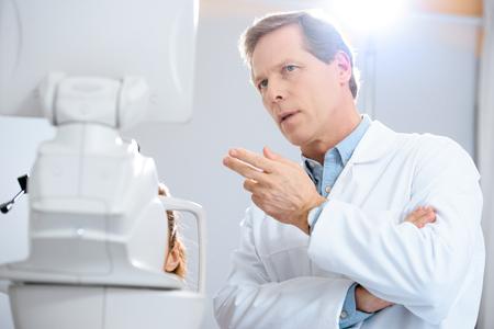 Guapo oftalmólogo gesticulando en consultorio