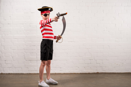 preteen boy with toy knife and gun in pirate costume