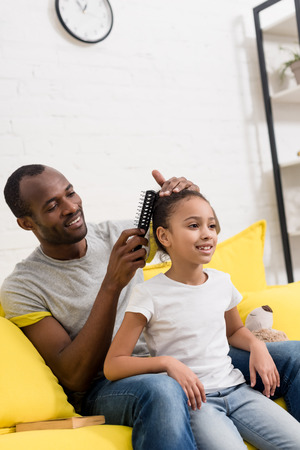 father combing hair of daughter while sitting behind her on couch Stock Photo