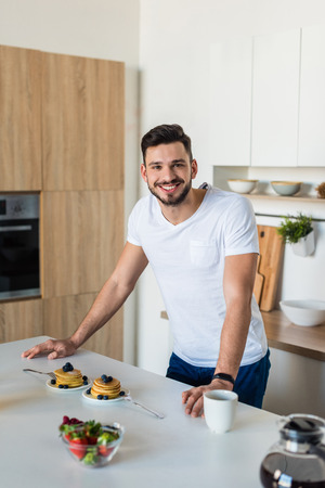 handsome young man leaning at kitchen table and smiling at camera at morning Stock Photo - 111692853
