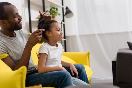 father combing hair of daughter while sitting behind her on couch Zdjęcie Seryjne