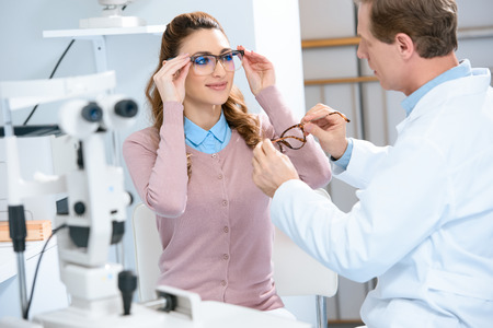 ophthalmologist helping patient choose glasses with needed lenses in clinic
