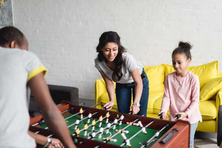 happy family playing table football together at home