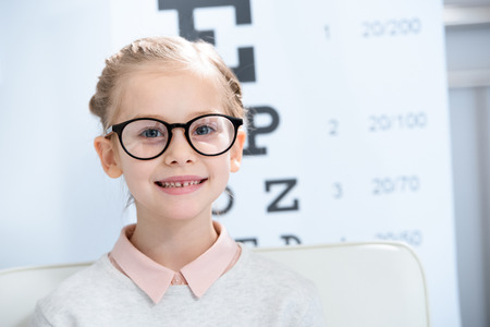 adorable child looking at camera in glasses at oculist consulting room