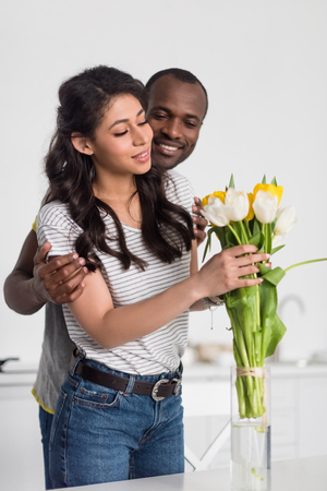 african american woman putting flowers bouquet into vase while her boyfriend embracing her from behind