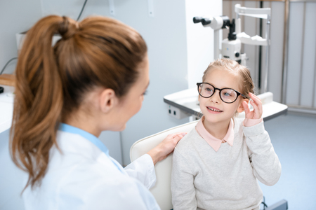 ophthalmologist and smiling kid in eyeglasses in optics