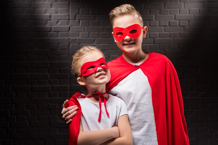 smiling siblings in red superhero costumes and masks Stock Photo