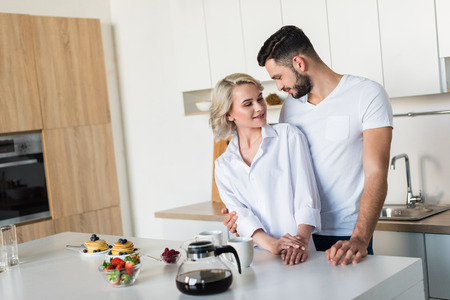 happy young couple smiling each other while having breakfast together