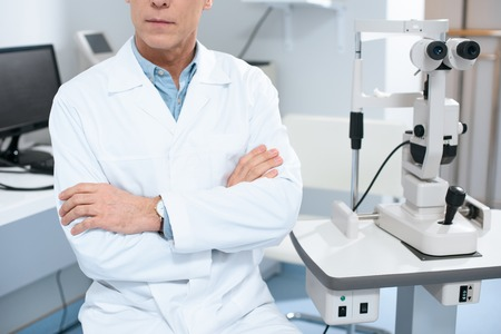 cropped image of ophthalmologist sitting with crossed arms near slit lamp in consulting room Stok Fotoğraf