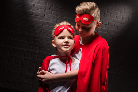 hugging siblings in superhero costumes and red masks