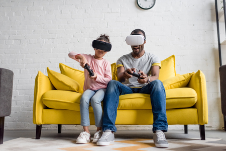 father and daughter in vr headsets playing video games on couch at home Stok Fotoğraf