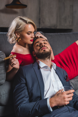 seductive young woman holding cigar and touching handsome man with glass of whisky