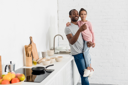 handsome father holding his daughter at kitchen and pointing somewhere