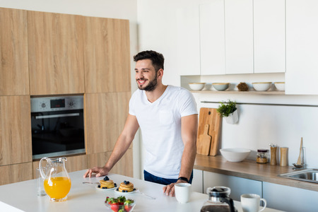 smiling young man leaning at kitchen table with breakfast and looking away
