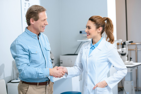 middle aged man shaking hands with female doctor after consultation in clinic