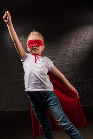 female child flying in red superhero mask