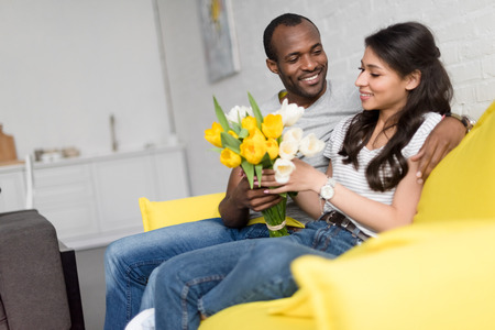 handsome man presenting bouquet of beautiful flowers to girlfriend