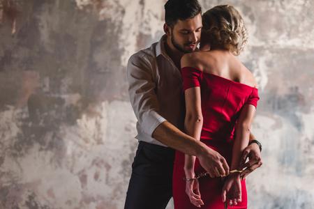 Apuesto joven poniendo esposas a mujer seductora en vestido rojo