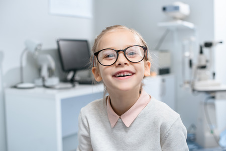 smiling little child in glasses in optical clinic Stock Photo - 111694743