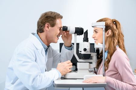 Seitenansicht des Augenarztes, der das Sehvermögen des Patienten mit Spaltlampe in der Klinik untersucht