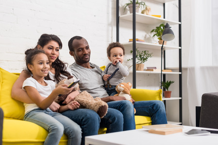young family watching tv together at living room