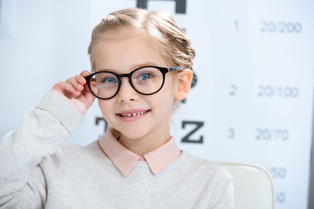 adorable smiling child looking at camera in glasses at oculist consulting room 免版税图像