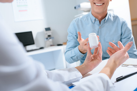 cropped view of doctor holding bottle of pills and talking with patient in clinic Stock Photo